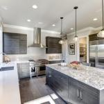 Pembroke Pines Modern gray kitchen features dark gray flat front cabinets paired with white quartz countertops and a glossy gray linear tile backsplash. Bar style kitchen island with granite counter.
